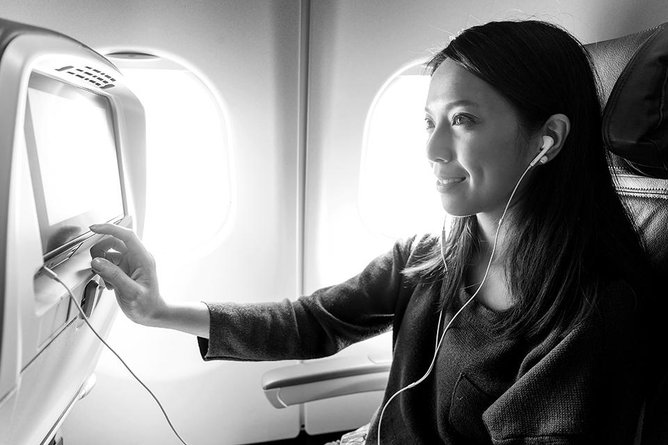 Frau bedient Bildschirm in Flugzeug
