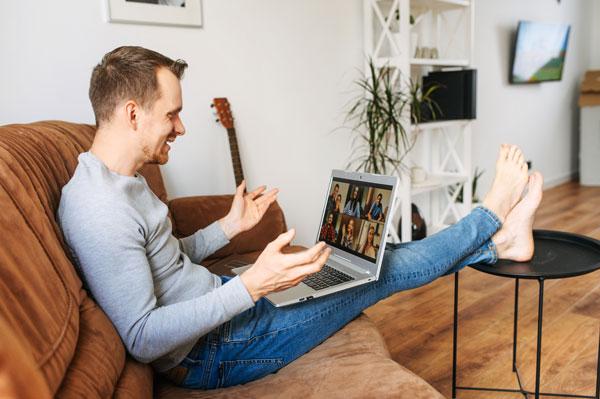 Mann sitzt gemütlich am Laptop bei einem Video Call